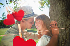 Composite image of cute smiling couple leaning against tree in the park Stock Photos