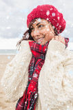 Composite image of cute smiling woman in warm clothing looking away at beach Stock Photos