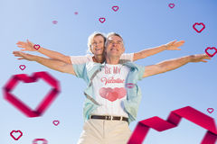 Composite image of cute valentines couple. Happy senior men giving his partner a piggy back against cute valentines message Royalty Free Stock Images