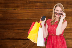 Composite image of cute woman holding shopping bags and her smartphone Stock Photo