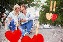 Composite image of cute young couple sitting on skateboard kissing Stock Photos