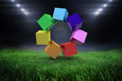 Composite image of 3d colourful cubes in a circle. 3d colourful cubes in a circle against football pitch with bright lights Royalty Free Stock Photography