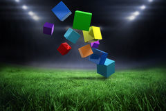 Composite image of 3d colourful cubes floating. 3d colourful cubes floating  against football pitch with bright lights Royalty Free Stock Image