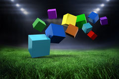 Composite image of 3d colourful cubes floating. 3d colourful cubes floating  against football pitch with bright lights Stock Images