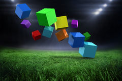 Composite image of 3d colourful cubes floating. 3d colourful cubes floating  against football pitch with bright lights Stock Photography