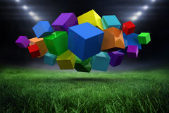 Composite image of 3d colourful cubes floating in a cluster. 3d colourful cubes floating in a cluster against football pitch with bright lights Stock Image