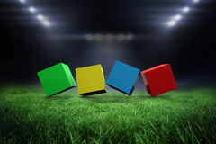 Composite image of 3d colourful cubes in a row. 3d colourful cubes in a row against football pitch with bright lights Royalty Free Stock Images