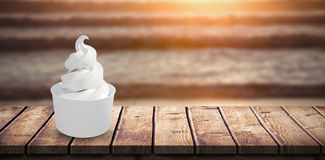 Composite image of 3d composite image of a cupcake. 3D Composite image of a cupcake against image of a sunset over the waves Royalty Free Stock Image