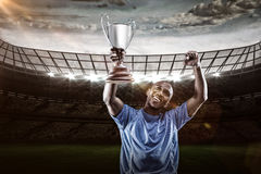 Composite image 3D of happy sportsman looking up and cheering while holding trophy Royalty Free Stock Photo