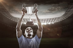 Composite image 3D of happy sportsman looking up while holding trophy Royalty Free Stock Image