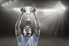 Composite image 3D of happy sportsman looking up while holding trophy Stock Photo
