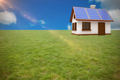 Composite image of 3d illustration of house with solar panels. 3d illustration of house with solar panels against scenic view of blue sky Royalty Free Stock Photo
