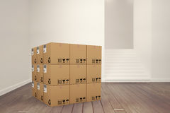 Composite image of 3d image of cardboard boxes. 3D image of cardboard boxes against empty room Royalty Free Stock Photography