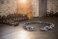 Composite image of 3d image of circular broken chain. 3d image of circular broken chain against dumbbells and kettlebell Royalty Free Stock Photos