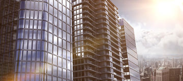 Composite image of 3d image of glass buildings. 3d image of glass buildings against city skyline Royalty Free Stock Photos