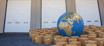 Composite image of 3d image of globe amidst cardboard boxes Stock Photography