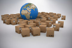 Composite image of 3d image of globe amidst cardboard boxes. 3D image of globe amidst cardboard boxes against grey background Royalty Free Stock Image