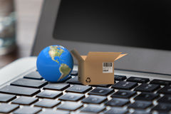 Composite image of 3d image of globe by cardboard box. 3D image of globe by cardboard box against close up of laptop with glass of water royalty free stock image
