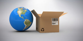 Composite image of 3d image of globe by cardboard box. 3D image of globe by cardboard box against grey background Royalty Free Stock Photography