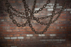 Composite image of 3d image of linked metallic chains hanging. 3d image of linked metallic chains hanging against brick wall royalty free illustration