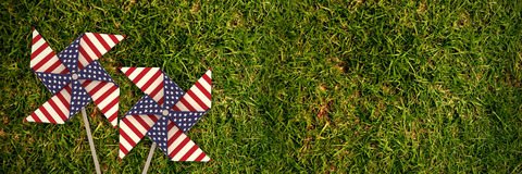 Composite image of 3d image of pinwheel toy with american flag pattern. 3D image of pinwheel toy with American flag pattern against full frame shot of grassy Royalty Free Stock Photos