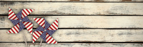 Composite image of 3d image of pinwheel toy with american flag pattern. 3D image of pinwheel toy with American flag pattern against wood panels in row Stock Images