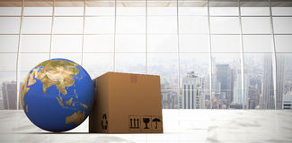 Composite image of 3d image of planet earth and box. 3D image of planet Earth and box against modern room overlooking city Royalty Free Stock Photography