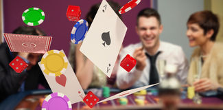 Composite image of 3d image of playing cards with casino tokens and dice. 3D image of playing cards with casino tokens and dice against winner and loser at Royalty Free Stock Images