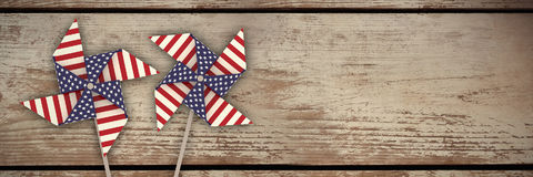 Composite image of 3d image composite of pinwheel with american flag pattern. 3D image composite of pinwheel with American flag pattern against wood panelling Stock Photo