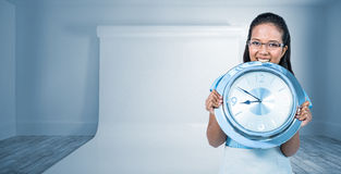 Composite image of delighted businesswoman holding a clock Royalty Free Stock Photos