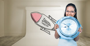 Composite image of delighted businesswoman holding a clock Royalty Free Stock Photo