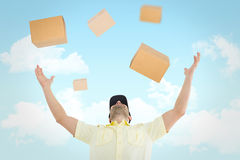 Composite image of delivery man with arms raised. Delivery man with arms raised against blue sky Stock Photo