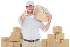 Composite image of delivery man with cardboard box gesturing thumbs up Stock Photo