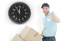 Composite image of delivery man with cardboard boxes gesturing thumbs up Royalty Free Stock Photography