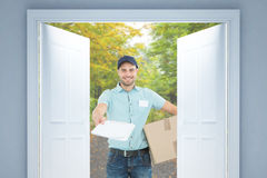 Composite image of delivery man with package giving clipboard for signature Stock Image
