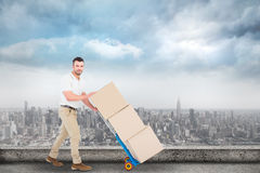 Composite image of delivery man pushing trolley of boxes Stock Photo