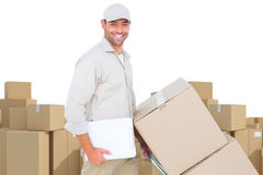 Composite image of delivery man pushing trolley of boxes on white background. Delivery man pushing trolley of boxes on white background against arrangements of Royalty Free Stock Images