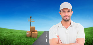 Composite image of delivery man standing arms crossed Stock Photography