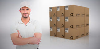 Composite image of delivery man standing arms crossed. Delivery man standing arms crossed against grey background Stock Photography