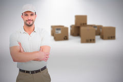 Composite image of delivery man standing arms crossed. Delivery man standing arms crossed against grey background Royalty Free Stock Photos