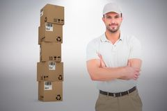 Composite image of delivery man standing arms crossed. Delivery man standing arms crossed against grey background Royalty Free Stock Images