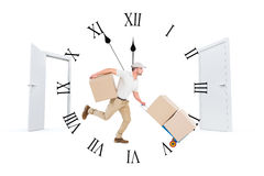 Composite image of delivery man with trolley of boxes running Royalty Free Stock Image