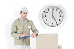 Composite image of delivery man writing on clipboard Stock Photography