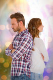 Composite image of depressed couple standing back to back. Depressed couple standing back to back  against glowing background Stock Image