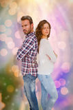 Composite image of depressed couple standing back to back. Depressed couple standing back to back against glowing background Royalty Free Stock Images