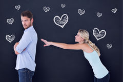 Composite image of desperate blonde reaching for boyfriend. Desperate blonde reaching for boyfriend against blackboard Stock Photography