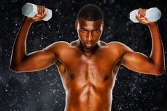 Composite image of determined fit shirtless man lifting dumbbells Royalty Free Stock Photography