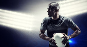 Composite image of determined rugby player holding ball Stock Image