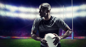 Composite image of determined rugby player holding ball Royalty Free Stock Photos