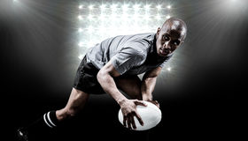 Composite image of determined sportsman looking away while playing rugby Royalty Free Stock Photo